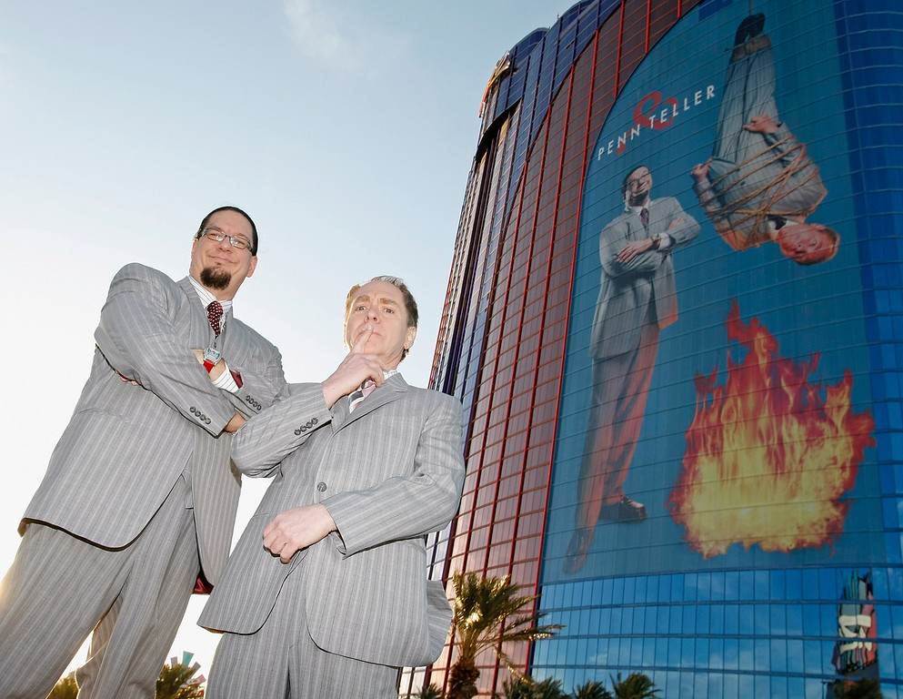 . LAS VEGAS - MARCH 3:  Penn Jillette (L) and Teller of the comedy/magic team Penn & Teller appear in front of a new 28-story tall building wrap of their likeness on the side of the Rio Hotel & Casino to celebrate the duo\'s 35 years performing together March 3, 2009 in Las Vegas, Nevada. The pair currently headlines a show at the Rio.  (Photo by Ethan Miller/Getty Images)