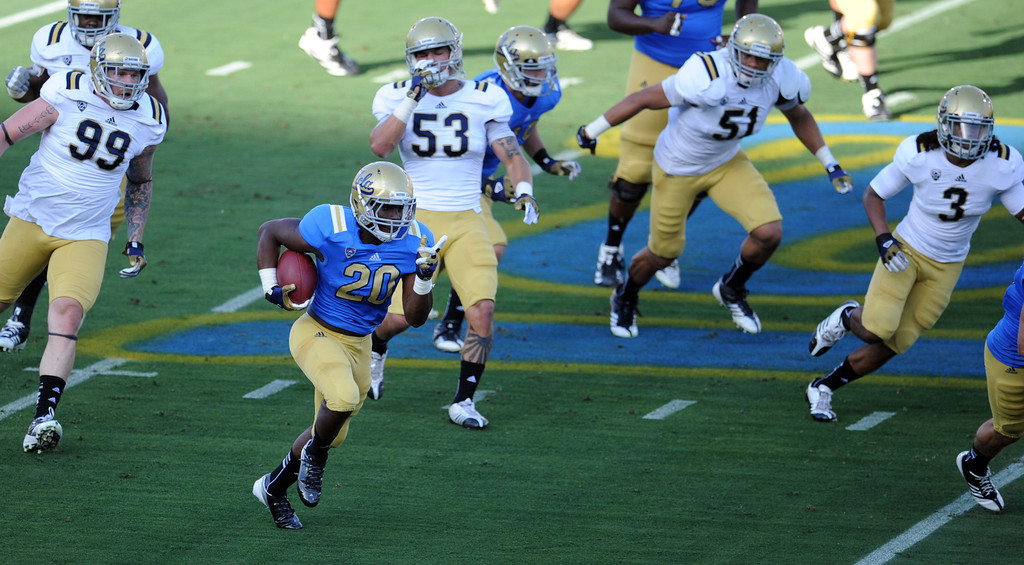 Description of . UCLA running back Melvin Emesibe (20) runs for yardage during the football spring showcase college football game in the Rose Bowl on Saturday, April 27, 2013 in Pasadena, Calif.    (Keith Birmingham Pasadena Star-News)