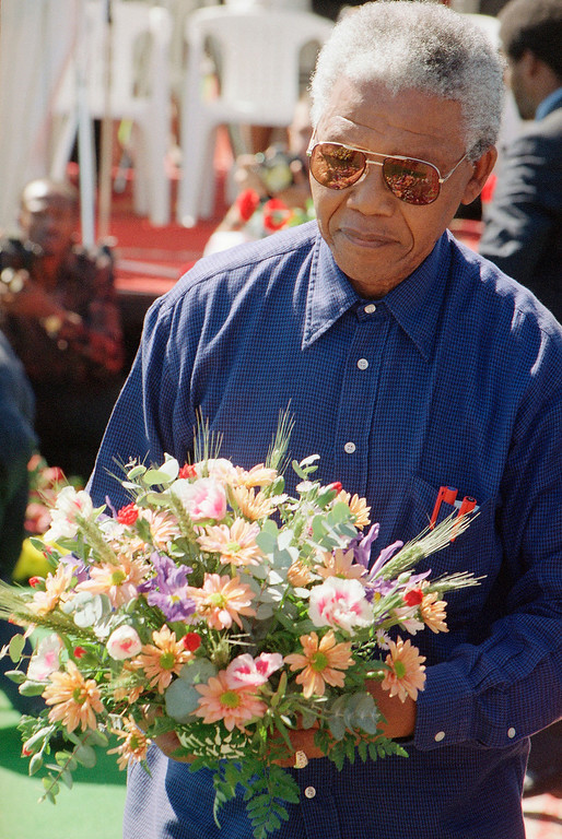 . President Nelson Mandela carries a wreath to lay at a memorial service held Saturday, April 15, 1995, for slain black South Africa Communist party leader Chris Hani who was assassinated two years ago. President Mandela, who delivered a speech at the service, and his estranged wife Winnie who also attended, didn\'t trade words, exchange glance, or acknowledge each other\'s presence.(AP Photo/Denis Farrell)