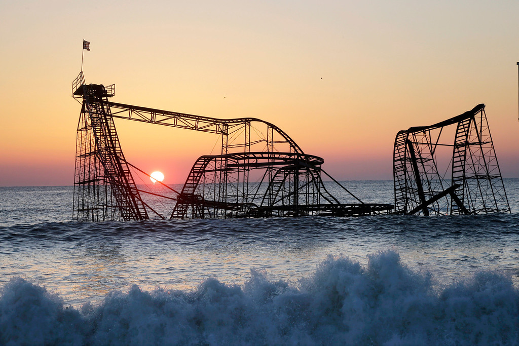 . The sun rises in Seaside Heights, N.J., Monday, Feb. 25, 2013, behind the Jet Star Roller Coaster which has been sitting in the ocean after part of the Funtown Pier was destroyed during Superstorm Sandy. The private owners of the amusement pier that collapsed in Seaside Heightsare working with insurers to devise a plan to dismantle the ride and get it out of the ocean. (AP Photo/Mel Evans)