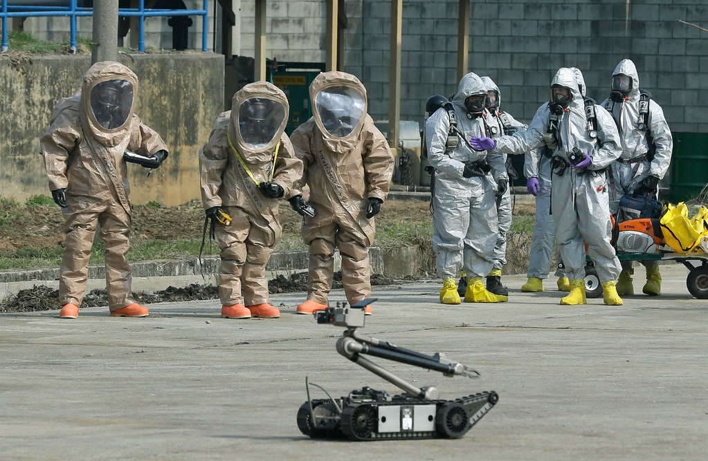 ". Soldiers of the U.S. Army 23rd chemical battalion, wearing anti-chemical suits, watch a bomb disposal robot during a demonstration of their equipment at a ceremony to recognize the battalion\'s official return to the 2nd Infantry Division based in South Korea at Camp Stanley in Uijeongbu, north of Seoul, Thursday, April 4, 2013. The 23rd chemical battalion left South Korea in 2004 and returned with some 350 soldiers in Jan. 2013. The battalion will provide nuclear, biological and chemical detection, equipment decontamination and consequence management assistance to support the U.S. and South Korean military forces. North Korea warned Thursday that its military has been cleared to attack the U.S. using ""smaller, lighter and diversified\"" nuclear weapons, while the U.S. said it will strengthen regional protection by deploying a missile defense system to Guam. (AP Photo/Lee Jin-man)"