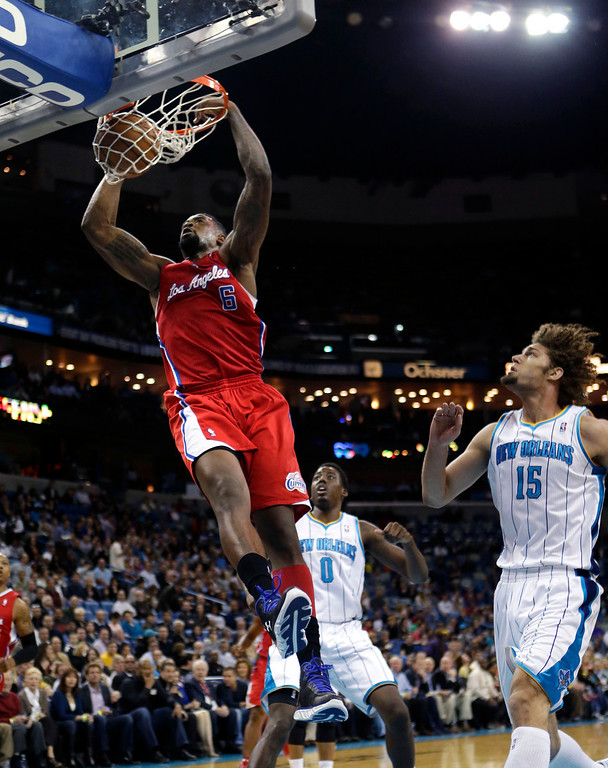 . Los Angeles Clippers center DeAndre Jordan (6) slam dunks in front of New Orleans Hornets center Robin Lopez (15) and forward Al-Farouq Aminu (0) in the first half of an NBA basketball game in New Orleans, Wednesday, March 27, 2013. (AP Photo/Gerald Herbert)