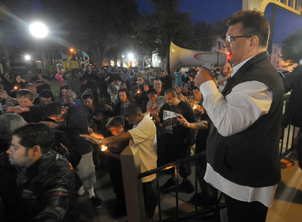. Pastor Jim Ortiz leads a prayer as residents gather for a community-wide prayer vigil at Central Park in Whittier in response to recent attempted child abductions on Friday March 15, 2013. About 150 people attended the candlelight vigil led by Pastor Sam Gamboa of the Good Shepherd Family Bible Church and organized by the Whittier Area Evangelical Ministerial Alliance. City and police officials joined citizens and area church members as they prayed for protection of the children and the arrest of the suspects. (SGVN/Staff Photo by Keith Durflinger)