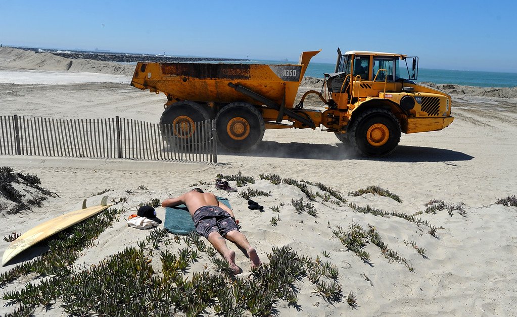 Description of . A surfer gets some sun as heavy machinery operates behind him to maintain the sand berm in the Peninsula neighborhood in Long Beach, CA on Wednesday, August 27, 2014. With city crews constantly building a sand berm, the water was held back from the homes and streets during the morning high tide. (Photo by Scott Varley, Daily Breeze)