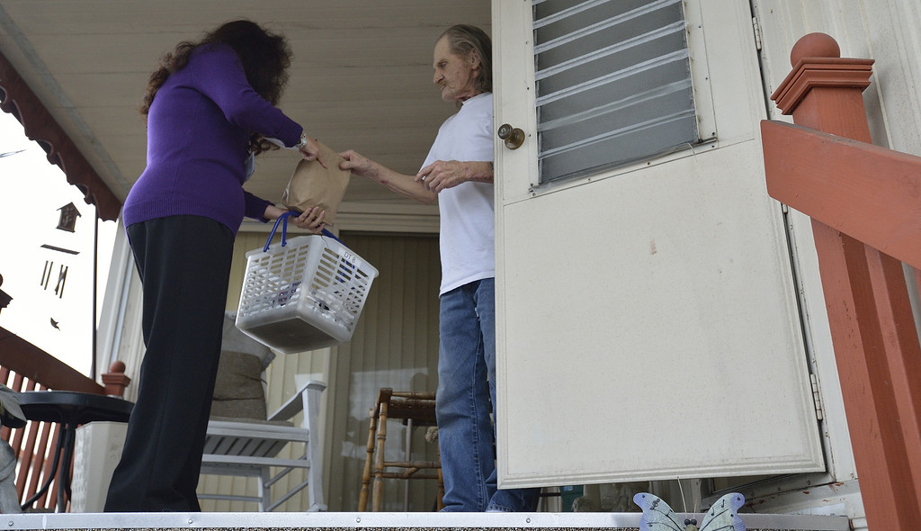 . LONG BEACH, CALIF. USA -- Meals on Wheels volunteer Rose Glidden delivers food to James Miller on February 19, 2013, in Long Beach, Calif.  Photo by Jeff Gritchen / Los Angeles Newspaper Group