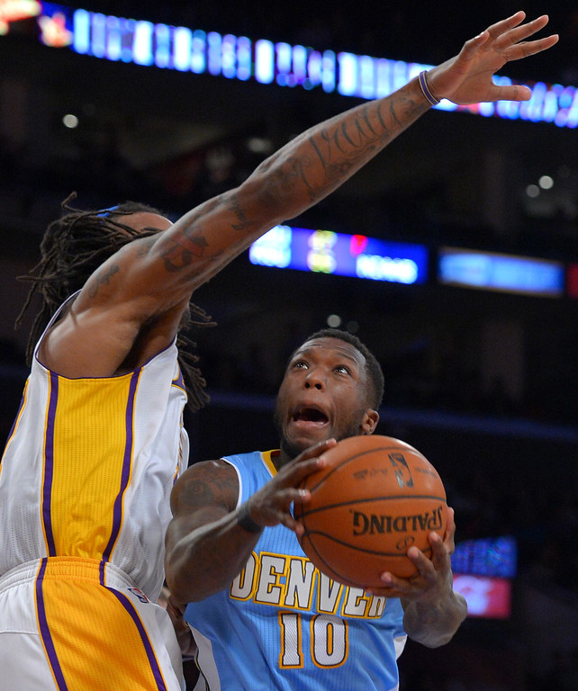 . Nuggets\' Nate Robinson sinks a difficult shot under the defense of Lakers\' Jordan Hill at the Staple Center in Los Angeles, CA on Sunday, January 5, 2014. 2nd half. Denver Nuggets beat the Lakers 137-115.  (Photo by Scott Varley, Daily Breeze)