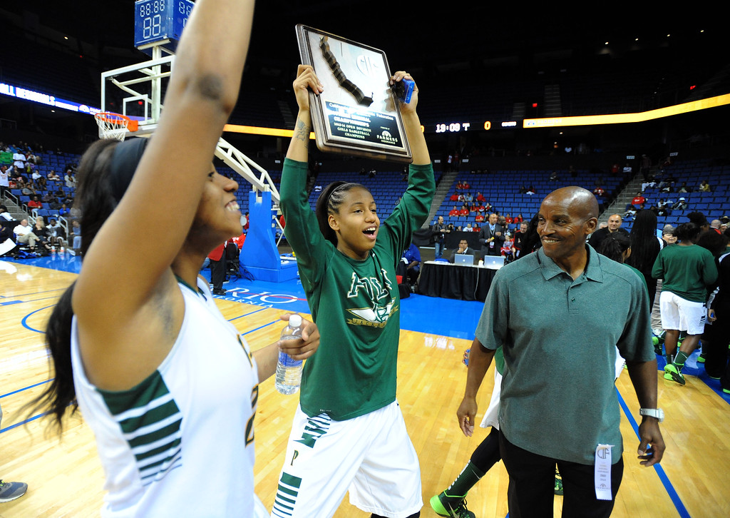 . Poly players and coach Carl Buggs celebrate with their championship plaque at Citizens Business Bank Arena in Ontario, CA on Saturday, March 22, 2014. Long Beach Poly vs Etiwanda in the CIF girls open division regional final. 2nd half, Poly won 56-46. Photo by Scott Varley, Daily Breeze)