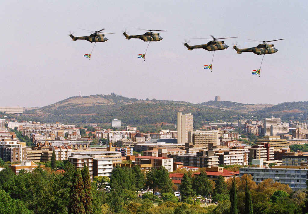 . South African Defense Force helicopters carrying the new South African flag fly over Pretoria during the inauguration ceremony for the country\'s first black president, Nelson Mandela in Pretoria, South Africa, May 10, 1994. The inauguration finished with a thunderous cannon salute, warplanes trailing smoke in the national colors of red, white, blue, black, green and gold, and these helicopters carrying the redesigned flag. (AP Photo)