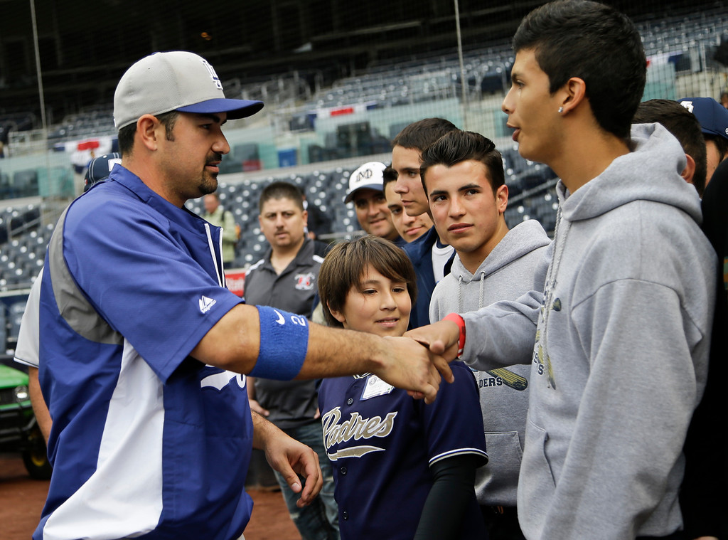 . Los Angeles Dodgers\' Adrian Gonzalez, left, greets the baseball team from Mater Dei High School before the Dodgers\' baseball game against the San Diego Padres in San Diego, Thursday, April 11, 2013. (AP Photo/Lenny Ignelzi)