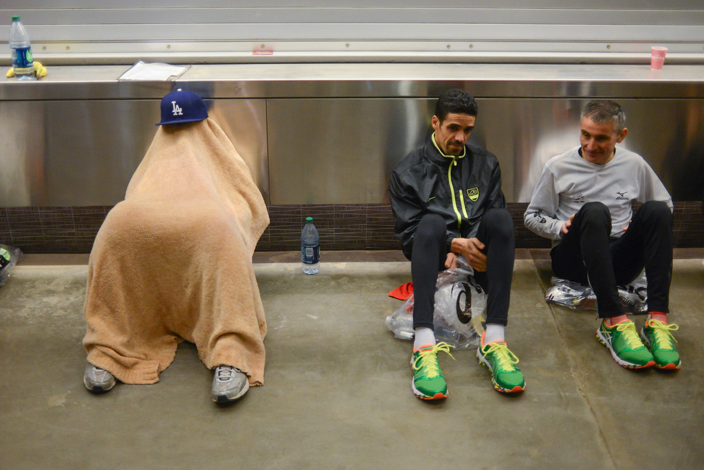 . Brent Rommel of Westminister tries to get some rest under a blanket before the start of the LA Marathon Sunday at Dodger Stadium. Photo by David Crane/Staff Photographer
