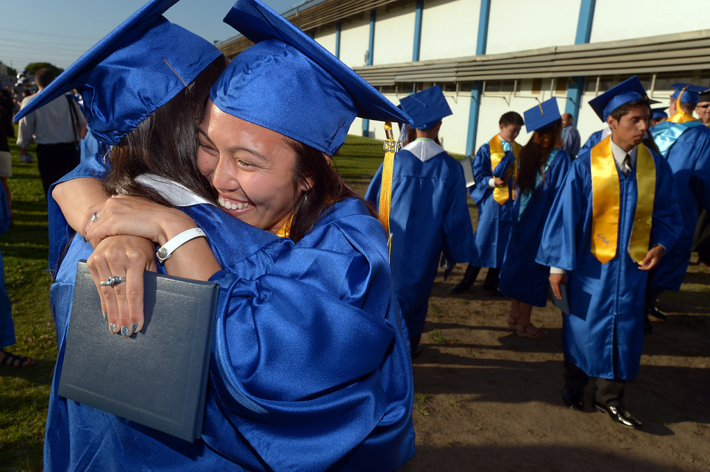 . Samantha Horito embraces her friend Kaitlyn Loeza after commencement ceremonies at North High School in Torrance Wednesday afternoon. The 2013 North High School commencement ceremonies take place on the school\'s football field in Torrance Wednesday afternoon.