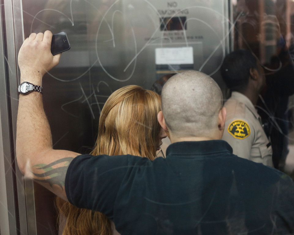 . Actress Lindsay Lohan, left, is shown through an elevator window covered by her body guard, as she arrives for trial at the Los Angeles Superior court Monday, March 18, 2013. Lohan is charged with three misdemeanor counts stemming from a crash on Pacific Coast Highway. She is charged with willfully resisting, obstructing or delaying an officer, providing false information to an officer and reckless driving. She is also accused of violating her probation in a misdemeanor jewelry theft case. (AP Photo/Damian Dovarganes)