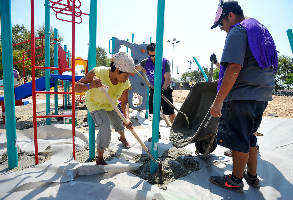 . More than 200 volunteers from  Mercer, Marsh and the Kiwanis pitch in to build a KaBOOM playground at Scott Park in Carson, CA on Thursday, August 7, 2014. The park will feature new play structures, planting beds and paint when completed. Teams of volunteers helped build the structures, mix concrete and move piles of mulch onto the playground surface. KaBOOM is a non-profit group that gets children to play by building playgrounds in impoverished communities and has built or improved more than 15,000 playgrounds since 1996.  (Photo by Scott Varley, Daily Breeze)