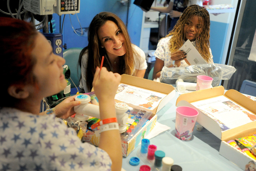 ". 04-18-2013-(LANG Staff Photo by Sean Hiller)-Toyota Grand Prix Celebrities visited Miller�s Children�s Hospital to visit the children they are raising money for through ""Racing for Kids.\"" Celebrity driver Kate del Castillo,center, visits with patients Cynthia Fuentes,left, and Precious Welch at Thursday\'s event."