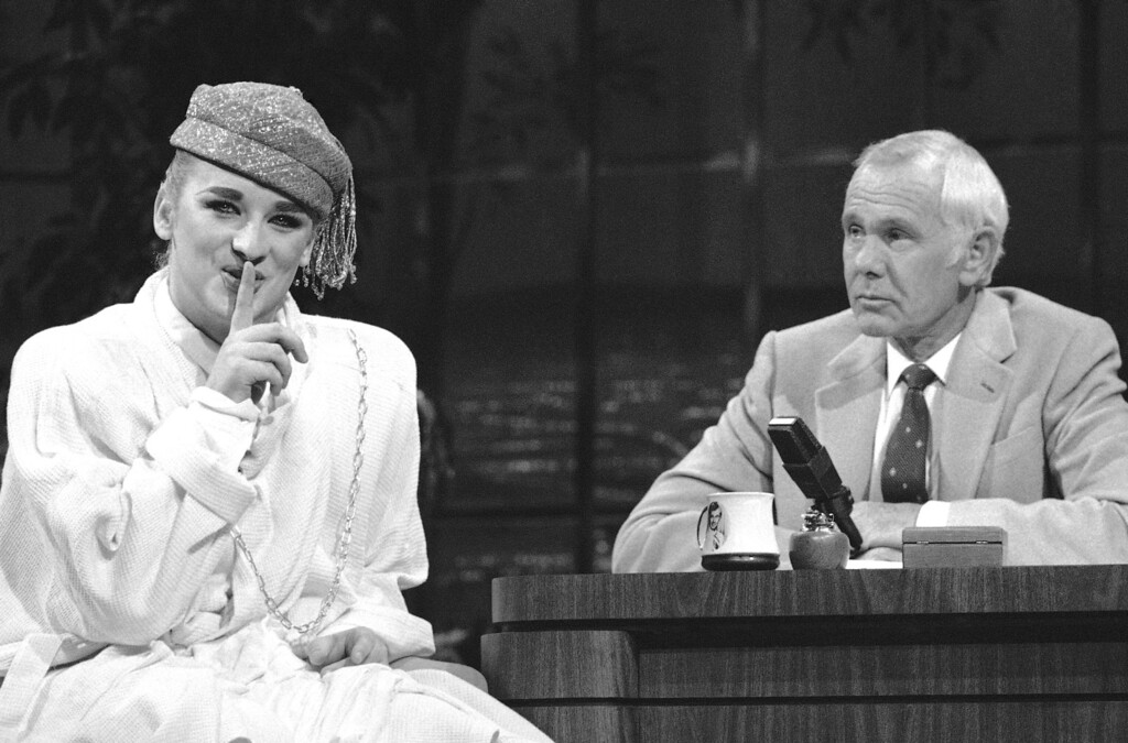 . British pop singer Boy George, left, gestures as talk show host Johnny Carson looks on during taping of the NBC Tonight Show in Burbank, California on Friday, Oct. 19, 1984. (AP Photo/Steve Bykes)
