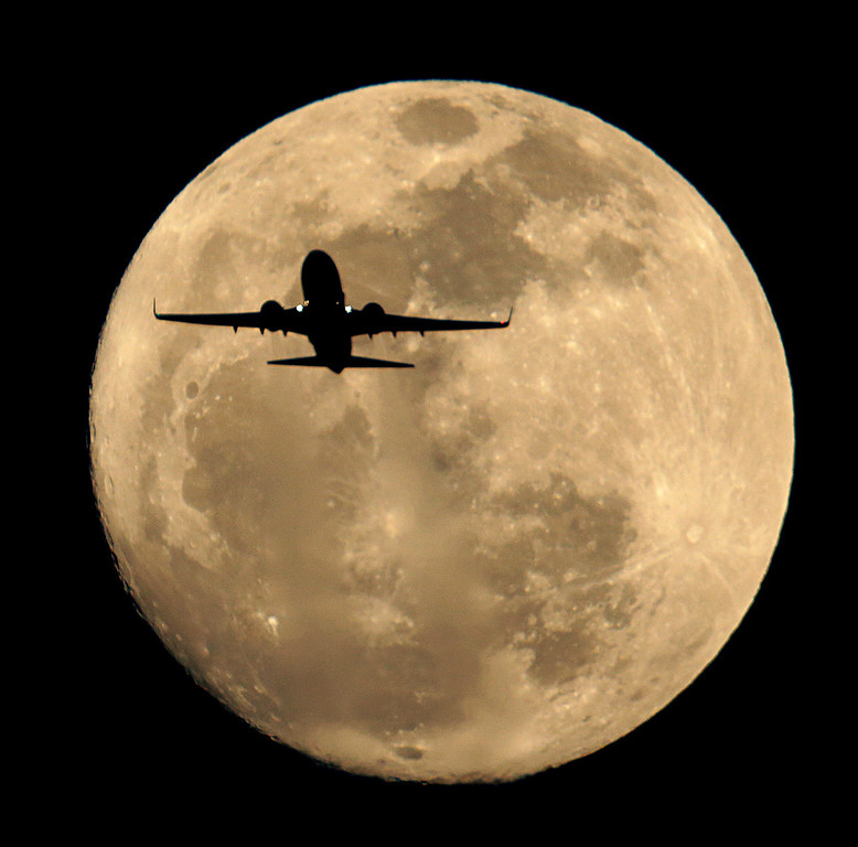 . A Southwest Airlines jet is silhouetted against the rising full moon as it takes of from Sky Harbor Airport Sunday, Feb. 24, 2013 in Phoenix. (AP Photo/Charlie Riedel)