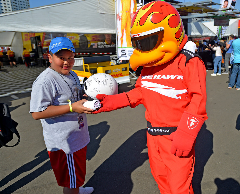 . 04-19-2013-(LANG Staff Photo by Sean Hiller)- Fans enjoy the Toyota Grand Prix in Long Beach. Justin Genilo,10, of Bellflower carries a race helmet to collect autographs.