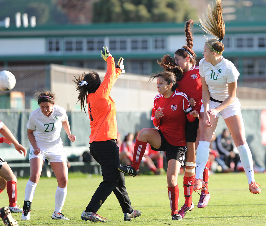 . 02-21-2012--(LANG Staff Photo by Sean Hiller)- South Torrance girls soccer beat Artesia 5-0 in Thursday\'s CIF Southern Section Division IV quarterfinal at South High. Jessica Nakae (27), left, scores a goal as  Artesia\'s goal keeper Celina Lopez anticipates the ball to go to Kyla Diekmann (10), right, in the second half . Diekmann completed a hat trick in the first half.