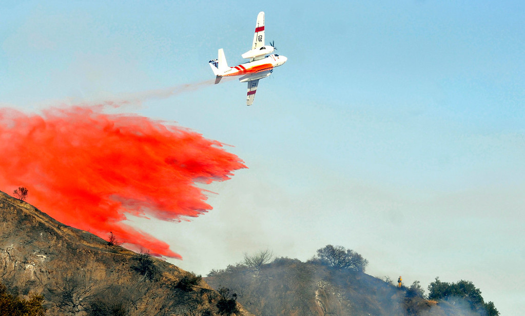 Description of . A lone firefighter is visible on the ridge ahead of the tanker plane.  Firefighters from all surrounding agencies came in to help the Monrovia Fire Dept. battle a major wildfire in the foothills above their city, Saturday April 20, 2013.  (Mike Mullen)