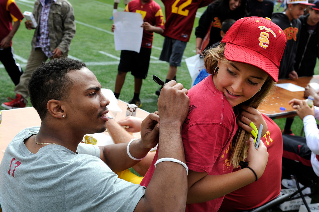 . CB Devian Shelton signs a shirt for Madison Grooters following USC\'s Spring Football Game at the L.A. Memorial Coliseum, Saturday, April 13, 2013. (Michael Owen Baker/Staff Photographer)