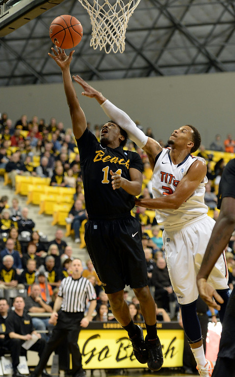 . Long Beach\'s Branford Jones (14) draws a foul from Fullerton\'s Chris Collins (32) in a Big West mens basketball game at the Pyramid Saturday, February 01, 2014, Long Beach CA.   Long Beach won 75-56. CSU Long Beach versus CSU Fullerton Photo by Steve McCrank/Daily Breeze