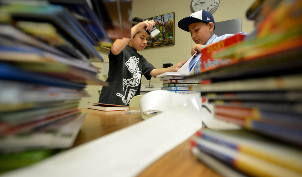 . 03-16-2013--(LANG Staff Photo by Sean Hiller)- Volunteers and students help the Anderson Elementary School Library sort and process new and donated books as well as spiff up campus with some colorful murals at Saturday\'s event organized by Access Books. Fifth graders Joseph Macias,11,left, and Oscar Echiveste,12, help to process new books in the library.