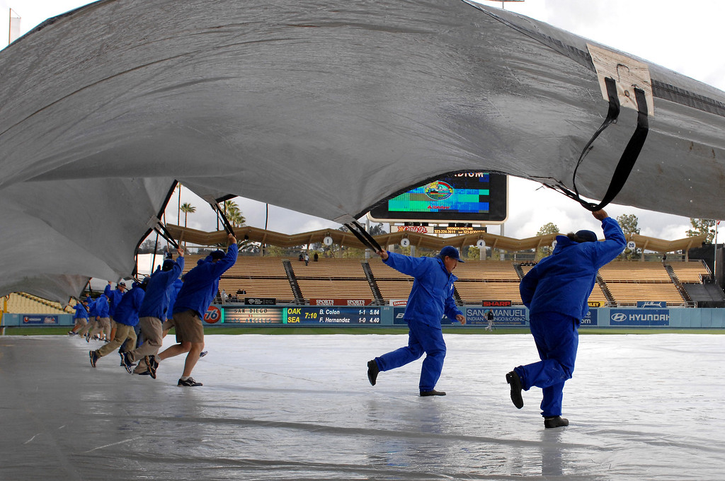 . Groundskeepers pull the tarp from the infield at Dodger Stadium, Friday, April 13, 2012, at Dodger Stadium. (Michael Owen Baker/Staff Photographer)