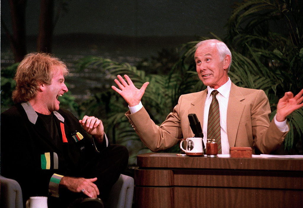 """. Comedian Robin Williams, left, laughs as talk show host Johnny Carson gestures during the second-to-last taping of the \""""Tonight Show\"""" at NBC Studios in Burbank, Calif., Thursday, May 21, 1992.  Williams presented Carson with a rocking chair as a retirement gift.  (AP Photo/Douglas C. Pizac)"""