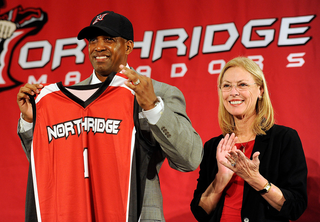 . Brandon Martin holds up a Northridge jersey as CSUN President Dianne F. Harrison  applauds. Martin, a former basketball player and senior associate athletic director at USC was named CSUN\'s new athletic director Monday, February 25, 2013. ( Hans Gutknecht/Staff Photographer)