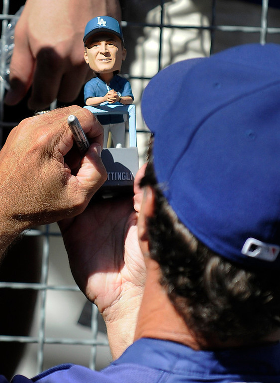 . Don Mattingly signs his bobble head before the game. The Dodgers ended the season on a high note with a 5-1 victory over the San Francisco Giants at Dodger Stadium. Los Angeles,CA 10/3/2012(photos by John McCoy/Staff Photographer)