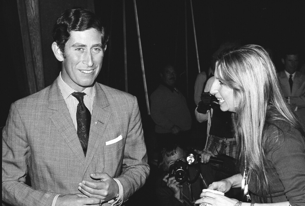 . U.S. actress and singer Barbara Streisand offers a cup of coffee to Prince Charles of Great Britain as they chat on a set at Warner Bros. studio in 