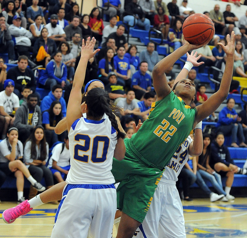 Description of . Long Beach Poly's Jada Matthews (22) drives to the basket past Bishop Amat's Janae Chamois (20) in the first half of a CIF State Southern California Regional semifinal basketball game at Bishop Amat High School on Tuesday, March 12, 2013 in La Puente, Calif. Long Beach Poly won 52-34.  (Keith Birmingham Pasadena Star-News)