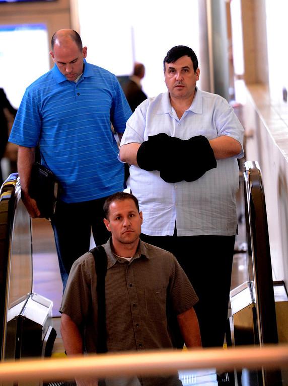 Description of . Former SBIA developer Scot Spencer is escorted by a San Bernardino County DA investigator and an FBI agent through the John Wayne Airport in Santa Ana March 28, 2013.   GABRIEL LUIS ACOSTA/STAFF PHOTOGRAPHER.