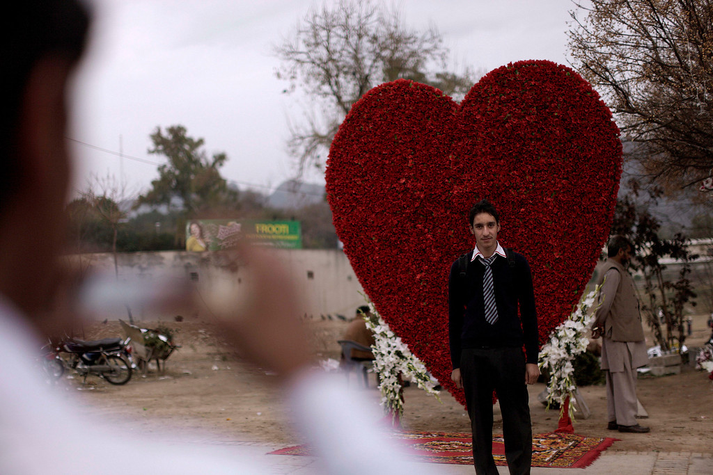 . A Pakistani youth poses for a picture taken by his friend in front of a big red heart made of flowers displayed outside flowers shop on Valentine\'s Day, in Islamabad, Pakistan, Thursday, Feb. 14, 2013. Romance may not be dead in Pakistan but it is under attack. Conservatives in Pakistan are attacking the romantic holiday as a western-inspired event helping to spread vulgarity in their country and putting up posters calling on people to boycott the holiday. But romantics are fighting back with an arsenal of flowers, pink teddy bears and heart-shaped balloons. (AP Photo/Muhammed Muheisen)
