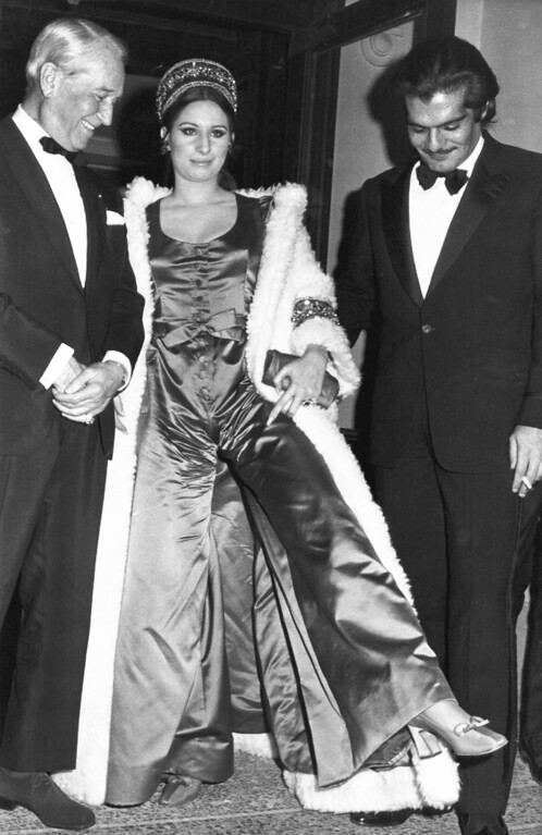 ". American singer Barbra Streisand shows off her red-satin evening trousers to French Singer Maurice Chevalier, left, and Egyptian actor Omar Sharif after the Premier of the film ""Funny Girl\"" at the Opera House, in Paris, Jan. 16, 1969. (AP Photo)"
