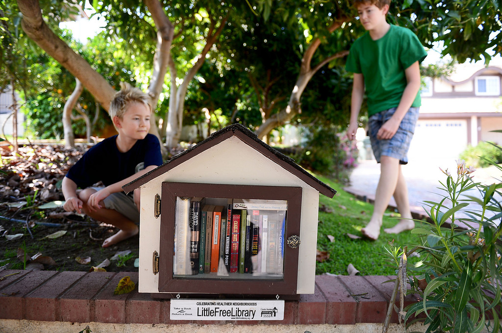 . Zach Szymkowski, 9, and his brother Jacob, 15, approach their Little Free Library on North Alta Vista Drive in Monrovia Friday, July 19, 2013. Their mom Sue Yost says they are meeting more neighbors since the library, created by Stephanie Cox, 18, for her Girl Scout Gold Award Project, went in last February. (SGVN/Staff Photo by Sarah Reingewirtz)