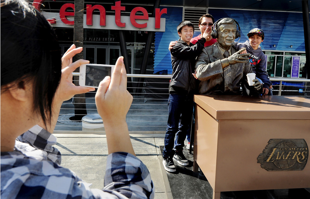 . Belle DeLong, of Los Angeles, photographs her family with a sculpture of Chick Hearn, former longtime play-to-play announcer for the Lakers, at the Staples Center in Los Angeles on Monday, February 18, 2013. Lakers owner Dr. Jerry Buss died today after a long battle with cancer. (SGVN/Photo by Walt Mancini/SXCity)