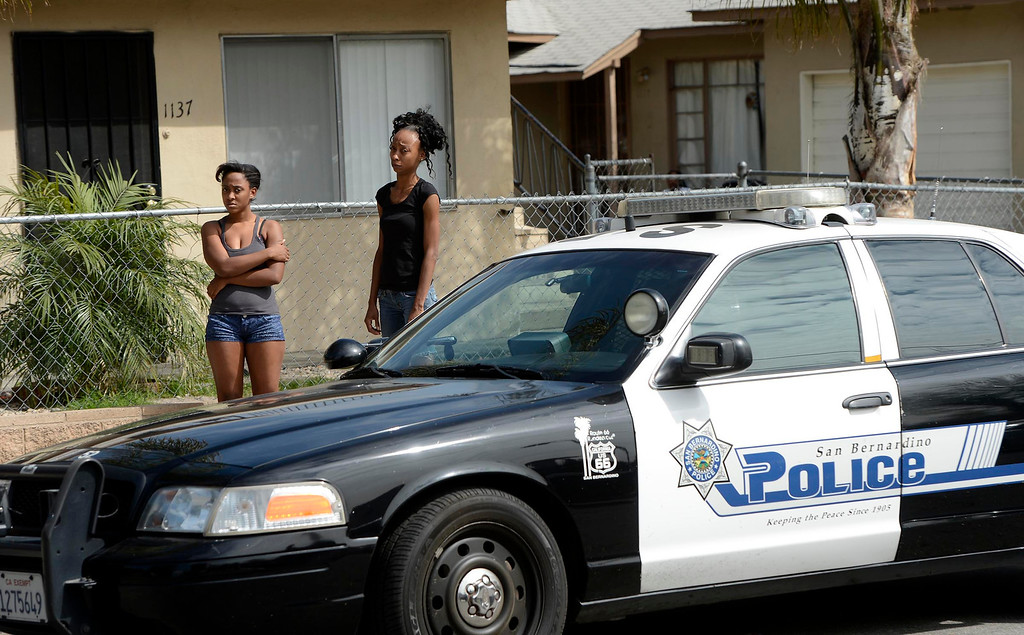 Description of . Two young women watch officers conduct a SMASH sweep along the 1100 block Mayfield Drive in San Bernardino April 4, 2013.  GABRIEL LUIS ACOSTA/STAFF PHOTOGRAPHER.