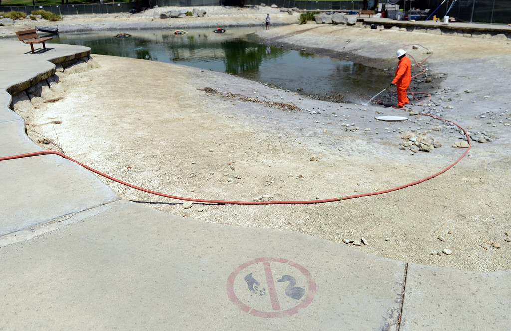 Description of . Crews continue to drain the lake at Red Hill Park in Rancho Cucamonga, CA, Friday, May 16, 2014. The city is draining the lake for cleaning and improvement of the infrastructure. (Photo by Jennifer Cappuccio Maher/Inland Valley Daily Bulletin)