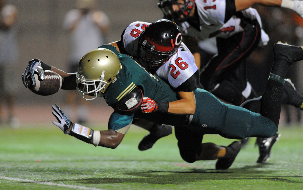 . Long Beach Poly football takes on Centennial (Corona) as part of the Mission Viejo Classic in Mission Viejo, CA on Friday, September 13, 2013. Long Beach Poly won 35-28.  Poly\'s John Smith dives across the goal line for a TD in the 4th qtr to tie the game. Centennial\'s Manu Nomura (26) tries to stop him. (Photo by Scott Varley, Press-Telegram)