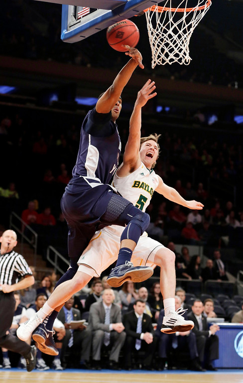 Description of . Brigham Young's Brandon Davies (0) blocks a shot by Baylor's Brady Heslip (5) during the first half of an NIT semifinal basketball game, Tuesday, April 2, 2013, in New York. (AP Photo/Frank Franklin)