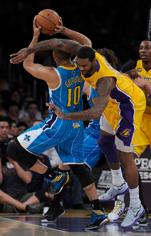 . Hornets#10 Eric Gordon is fouled by Lakers#6 Earl Clark in the first half. The Lakers played the New Orleans Hornets at Staples Center in Los Angeles CA 4/9/2013(John McCoy/Staff Photographer