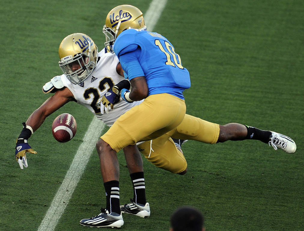 Description of . UCLA cornerback Anthony Jefferson (23) breaks-up a pass intenedted for Kenneth Walker (10) during the football spring showcase college football game in the Rose Bowl on Saturday, April 27, 2013 in Pasadena, Calif.    (Keith Birmingham Pasadena Star-News)