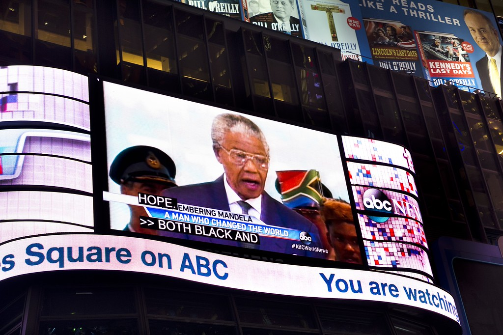 . A large television screen in New York\'s Times Square broadcasts a news show as they announce the death of Nelson Mandela, former South African president and anti-apartheid leader, December 5, 2013.        (STAN HONDA/AFP/Getty Images)