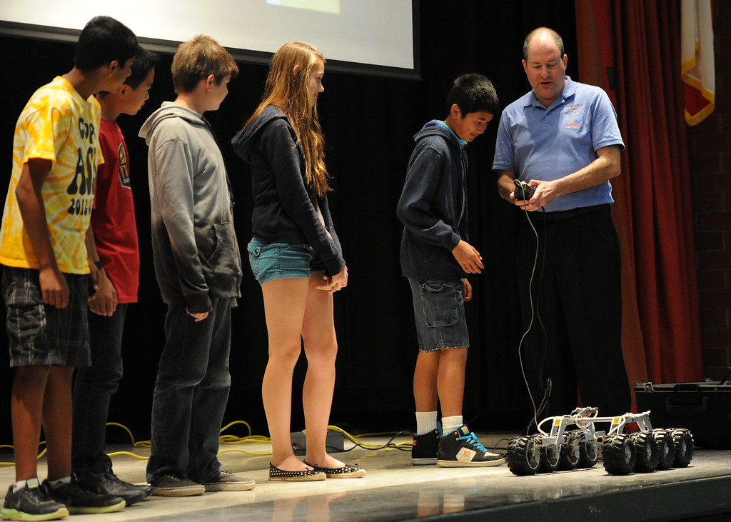 Description of . (John Valenzuela/Staff Photographer)  Brian Cooper, lead rover driver of Curiosity, shows eight graders from Cope Middle School in Redlands a small robot version of a rover during his visit on Friday, April 19, 2013.  Cooper is the worlds first Mars rover driver and has worked on every rover mission sent to Mars.