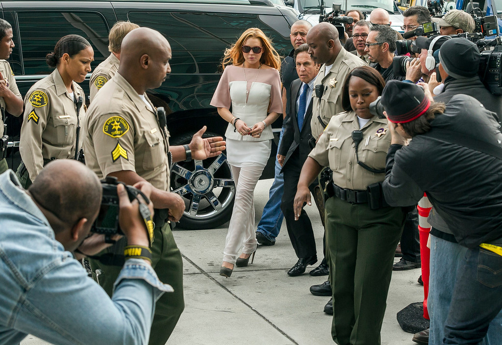 . Actress Lindsay Lohan walks with her attorney Mark Heller, for her trial Monday, March 18, 2013 at Los Angeles Superior court. Lohan is charged with three misdemeanor counts stemming from a crash on Pacific Coast Highway. She is charged with willfully resisting, obstructing or delaying an officer, providing false information to an officer and reckless driving. She is also accused of violating her probation in a misdemeanor jewelry theft case. (AP Photo/Damian Dovarganes)
