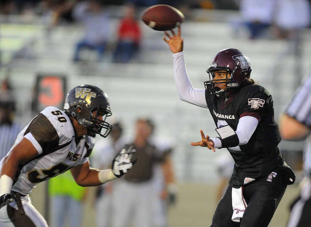 . West High takes on Torrance in a non league football game at Zamperini Stadium in Torrance, CA on Thursday, September 12, 2013. Under pressure from West defender Ray Lima, Torrance QB Gabe Gonsalves is forced to dump the ball off. (Photo by Scott Varley, Daily Breeze)