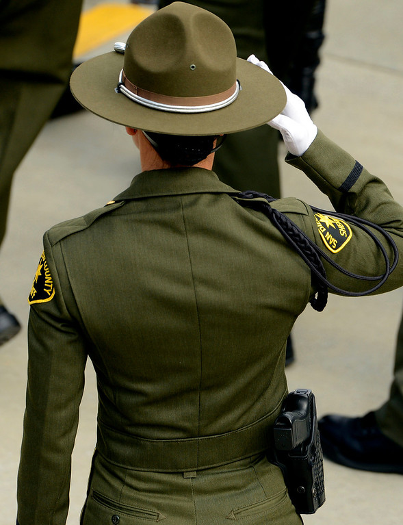 Description of . A San Diego County Sheriff Deputy salutes the casket of San Bernardino County Sheriff Deputy Jeremiah MacKay during memorial services held at the San Manuel Amphitheater in Devore February 21, 2013.  GABRIEL LUIS ACOSTA/STAFF PHOTOGRAPHER.