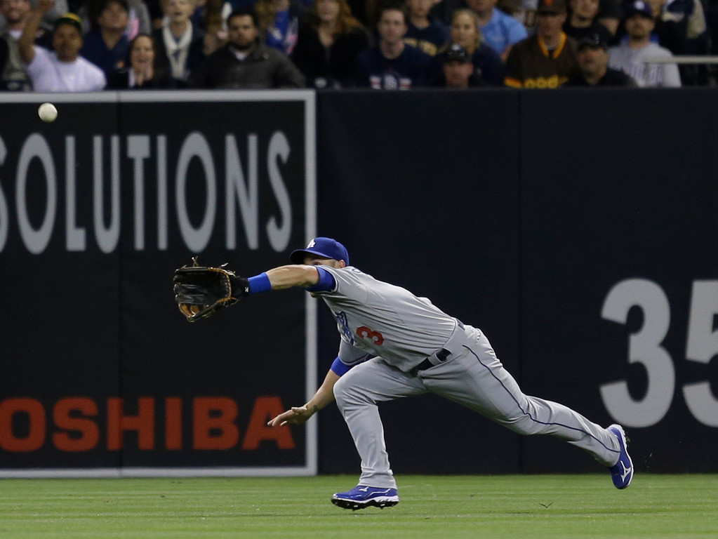 . Los Angeles Dodgers left fielder Skip Schumaker makes a diving catch to rob San Diego Padres\' Mark Kotsay of a base hit with two runners on base in the eighth d inning of a baseball game in San Diego, Wednesday, April 10, 2013. (AP Photo/Lenny Ignelzi)