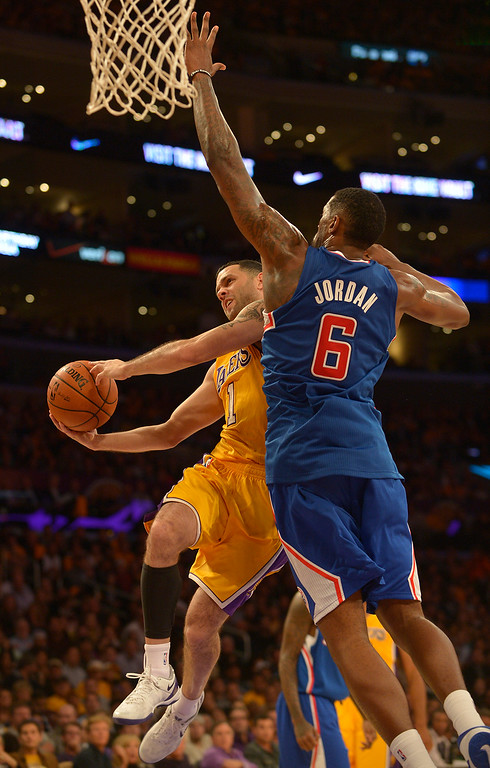 . Lakers#1 Jordan Farmar goes to the hoop against Clippers#6 DeAndre Jordan. The Los Angeles Lakers defeated the Clippers 116 to 103 in the opening game of the season at Staples Center. Los Angeles, CA. 10/29/2013. photo by (John McCoy/Los Angeles Daily News)